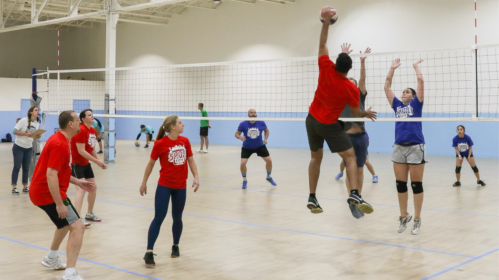 A group of men and women play indoor volleyball