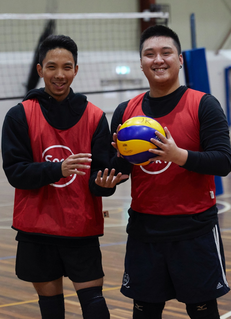 Two men standing holding volleyballs