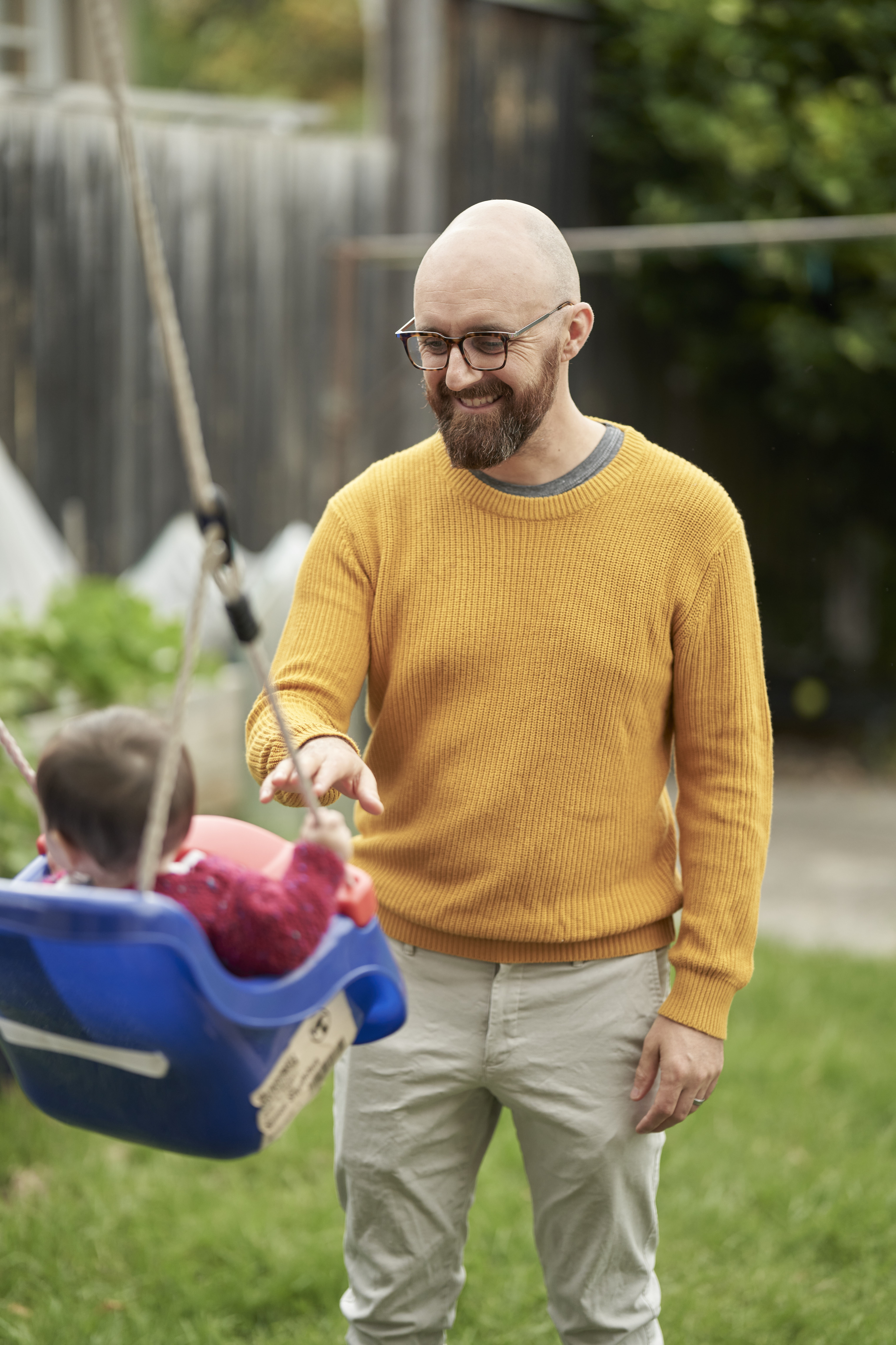 Simon pushing baby Margie on a swing in a backyard. Simon is wearing a yellow jumper and smiling