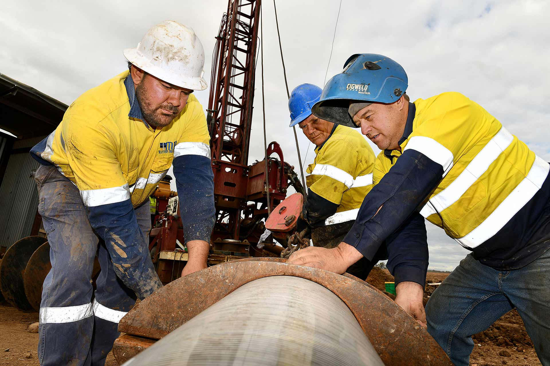 3 men operating a water drilling machine