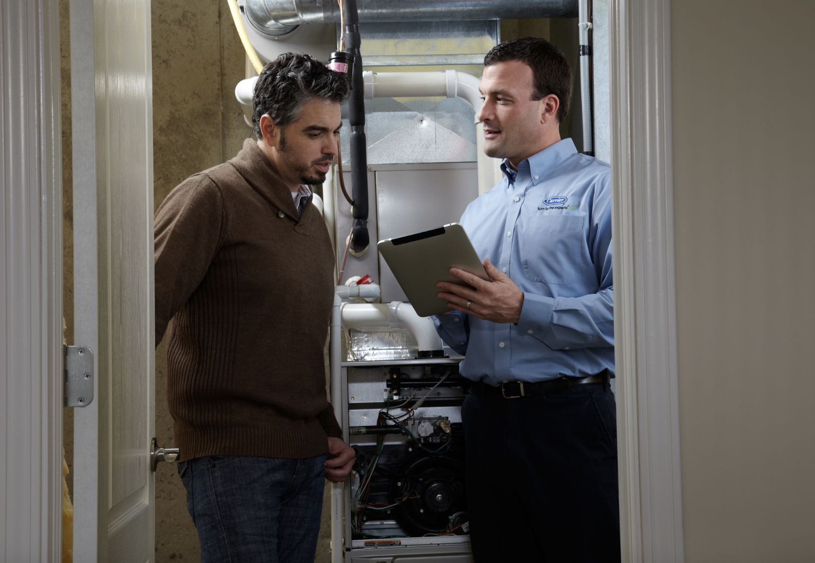 Boiler repairman reviewing checklist with a client
