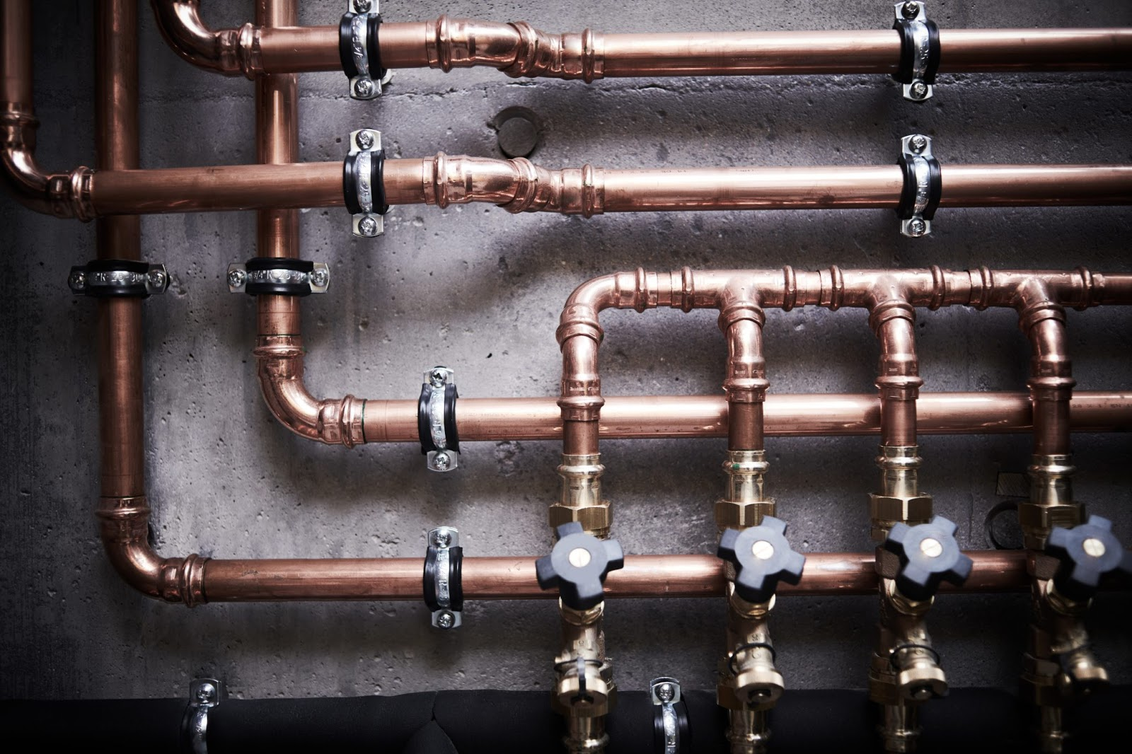 intertwined copper piping with faucets