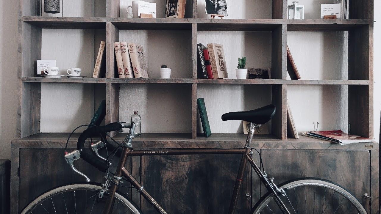 bike up against bookshelf books plants dark wood white walls