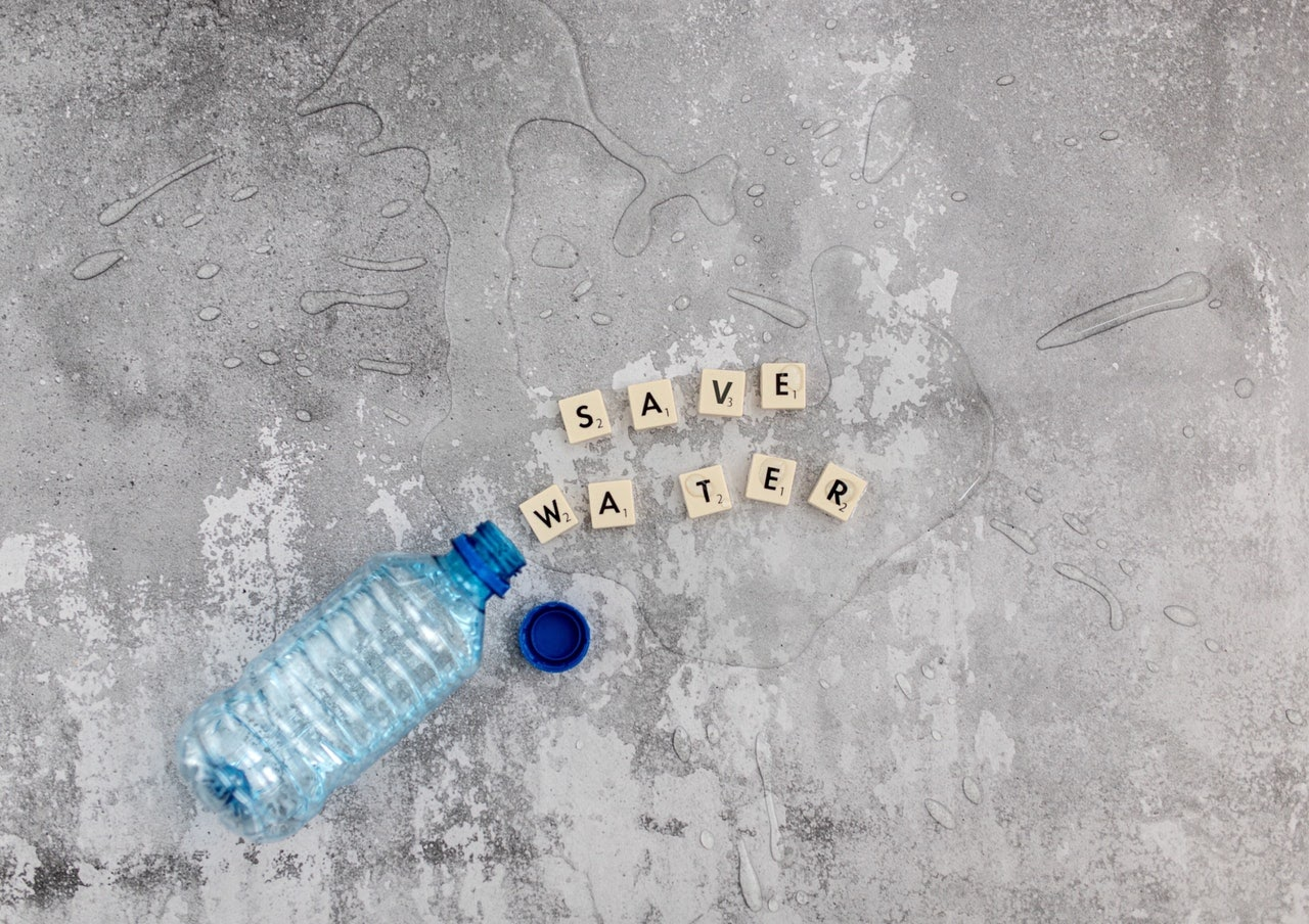 water bottle save water cubes spilled grey background