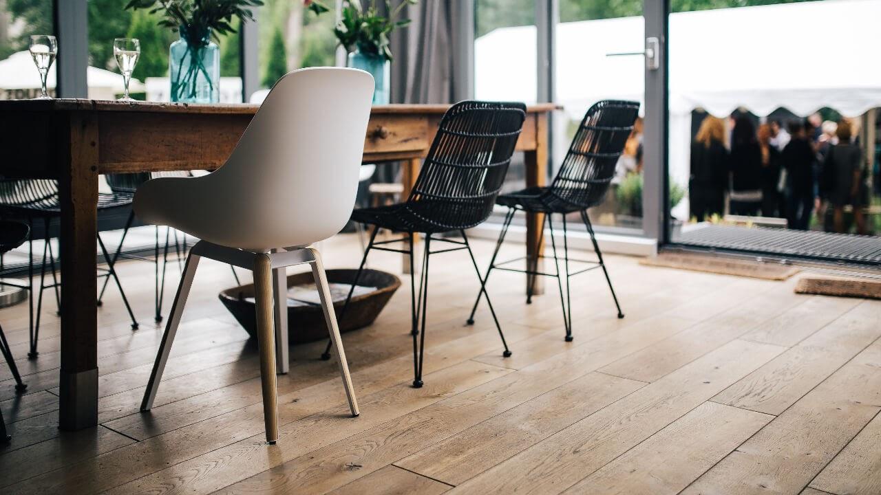 modern living area wooden floors door open table chairs