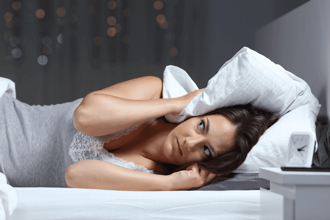 woman lying in bed hearing noises pillow over ears looking around concerned alarm clock