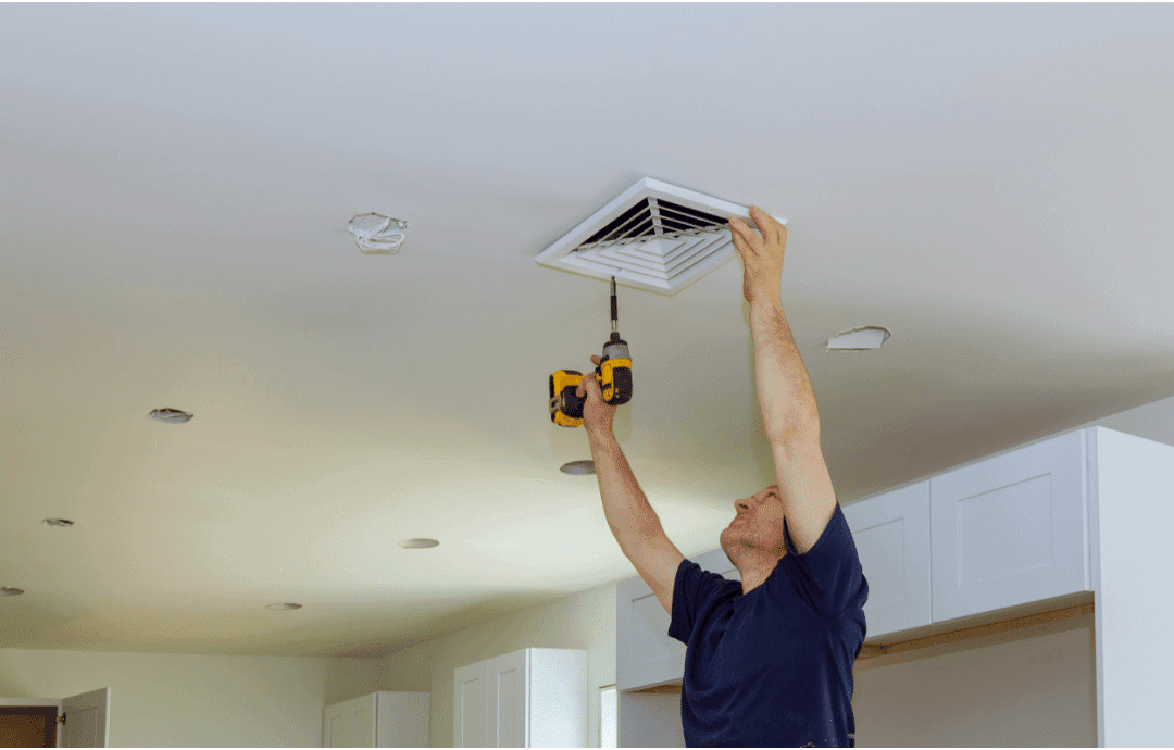 man repairing air vent in ceiling in kitchen drill blue shirt
