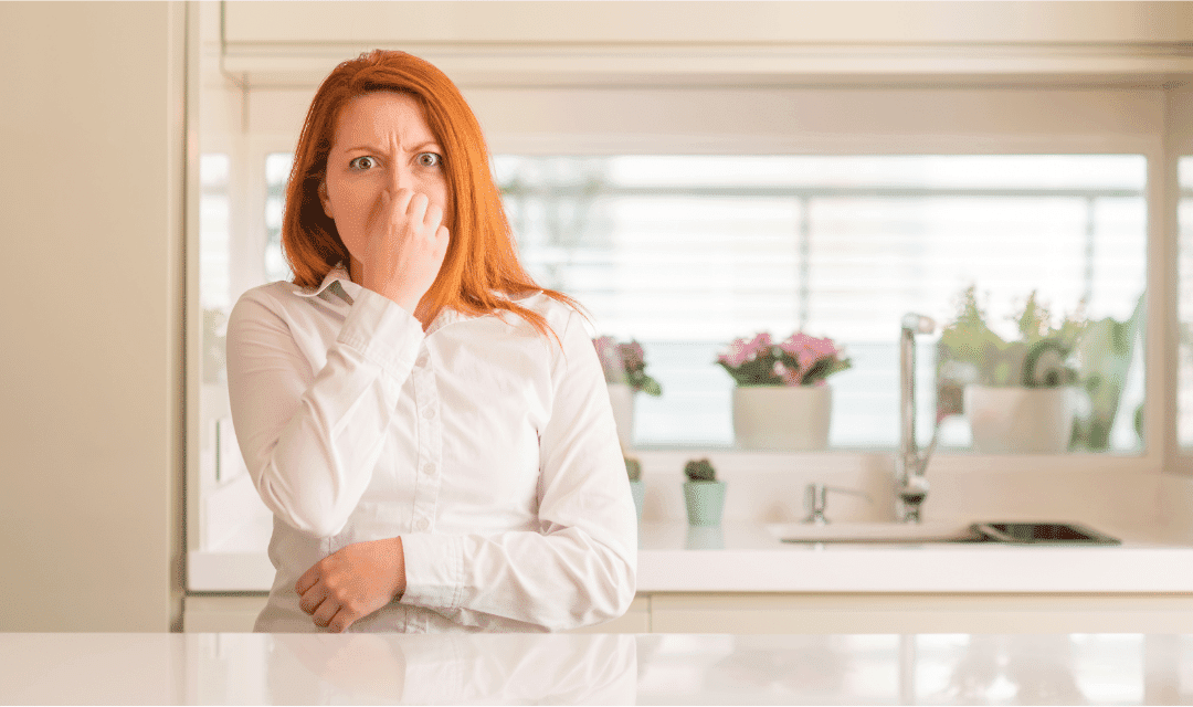 woman holding nose bad smell red hair in white kitchen white shirt