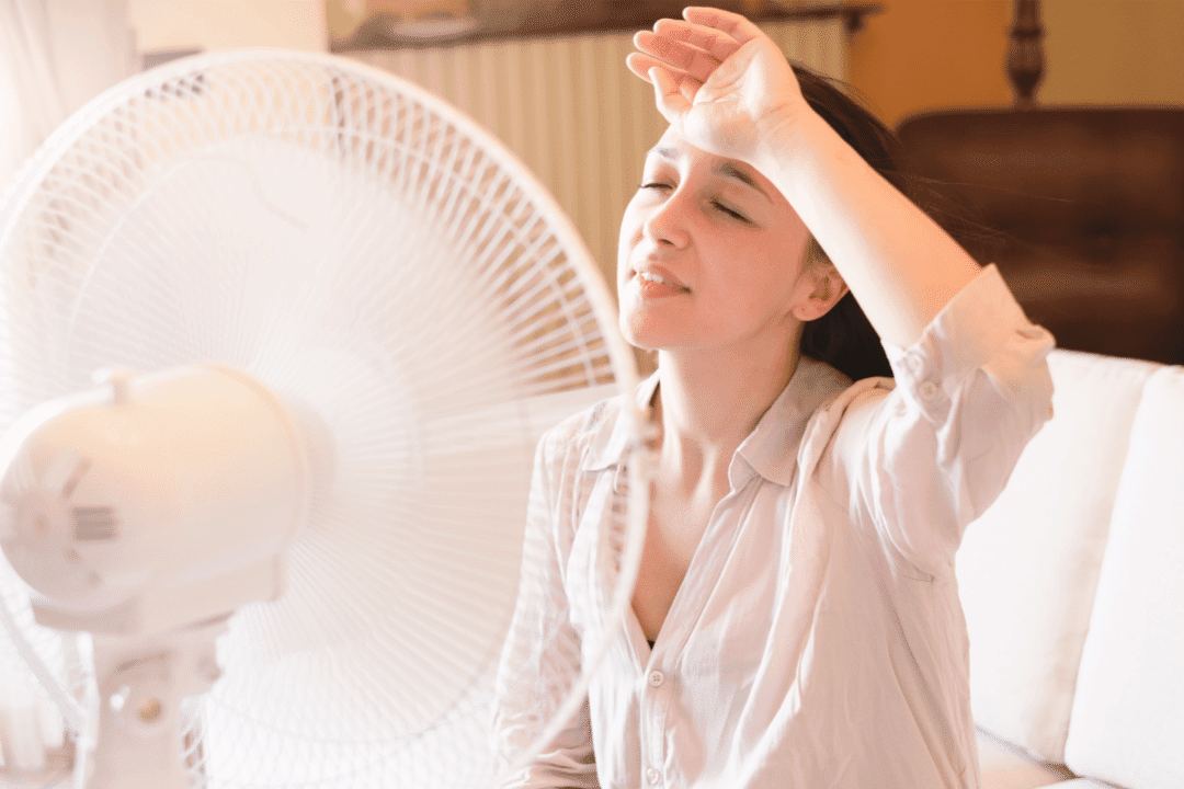 woman with fan excess heat overheating inside poor air conditioning beige shirt white couch