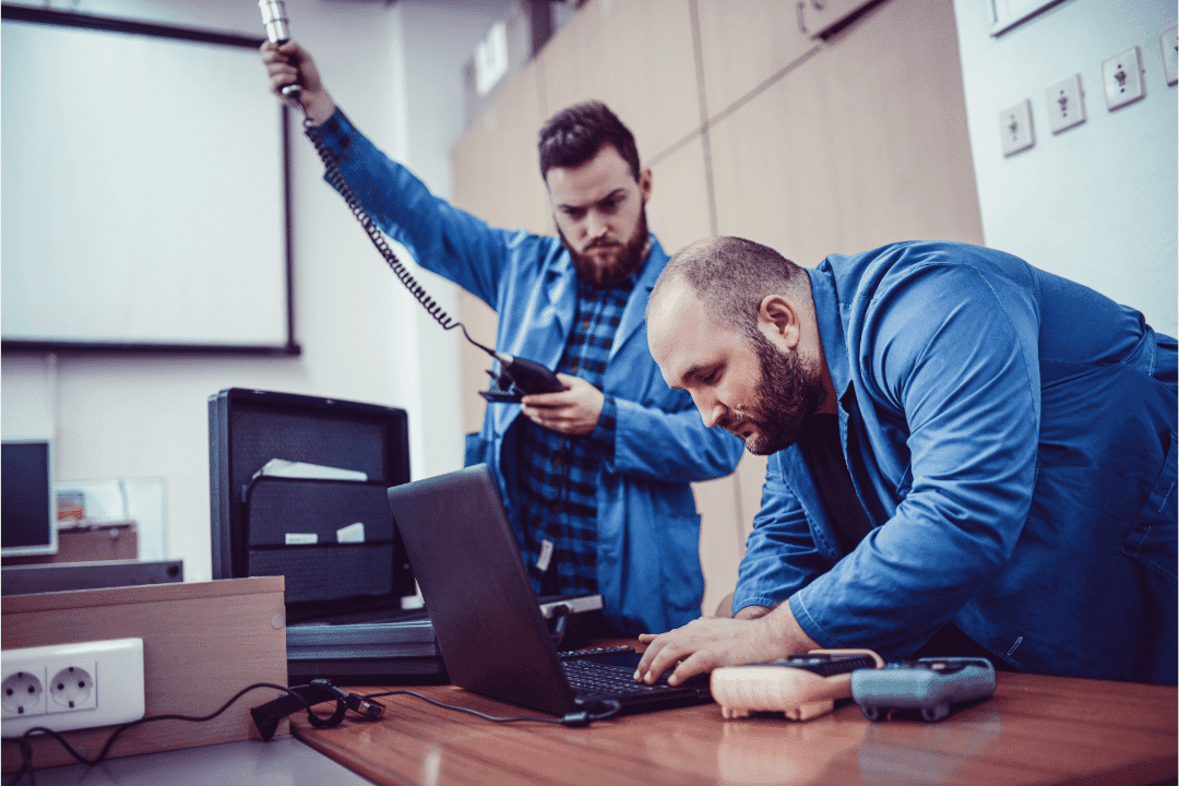 two men testing air quality in a building with a machine reading data denim jackets observation