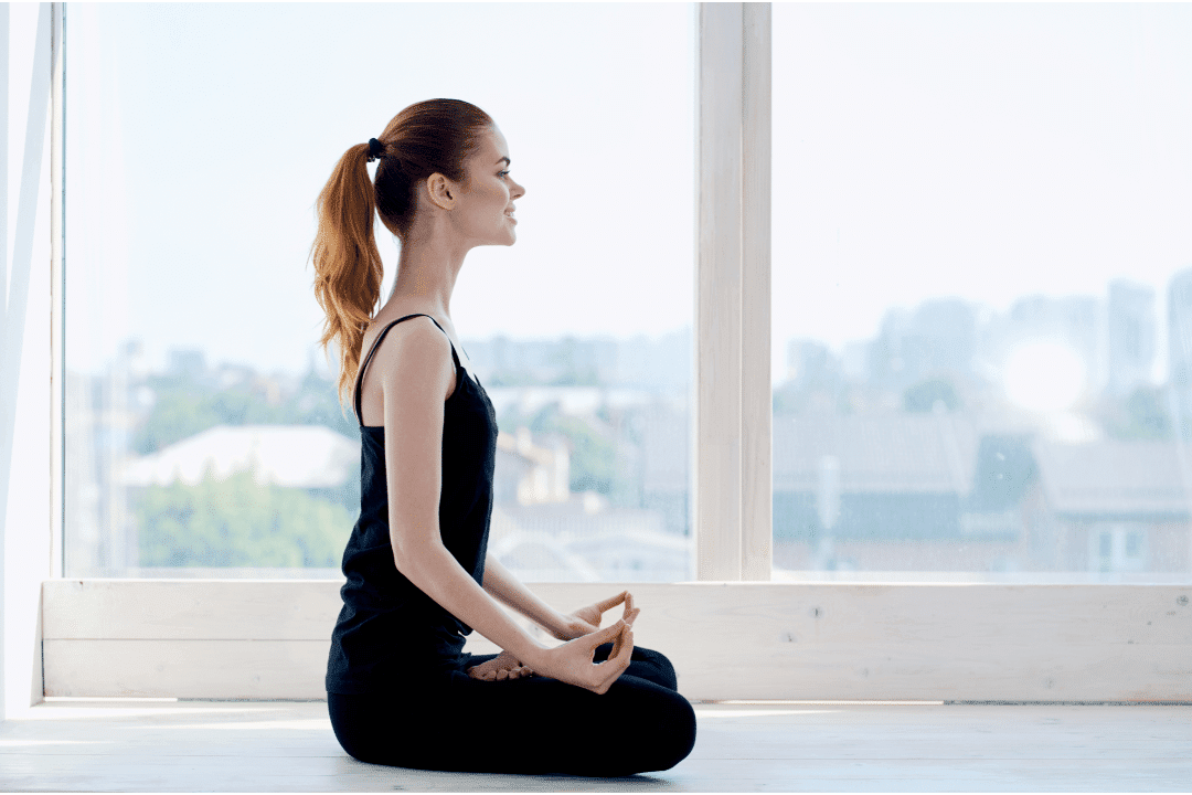 woman doing yoga cityscape in the background deep breathing large window black clothing red hair sunny day ponytail