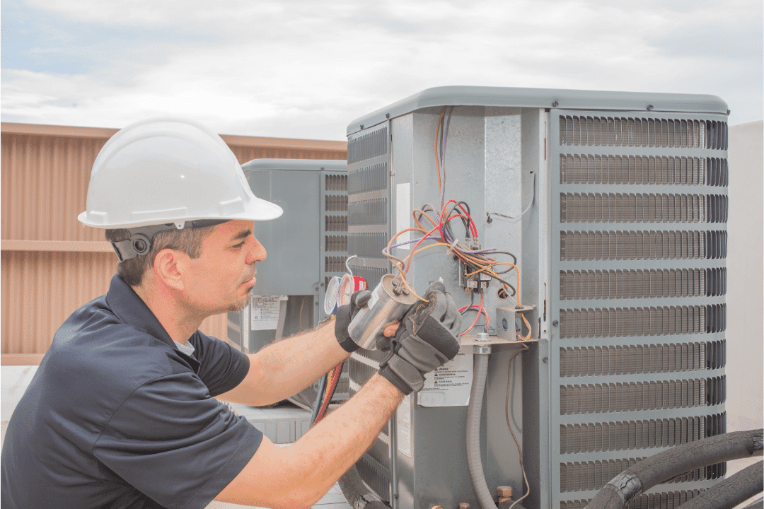 technician repairing HVAC on rooftop hard hat air conditioner wires gloves polo shirt