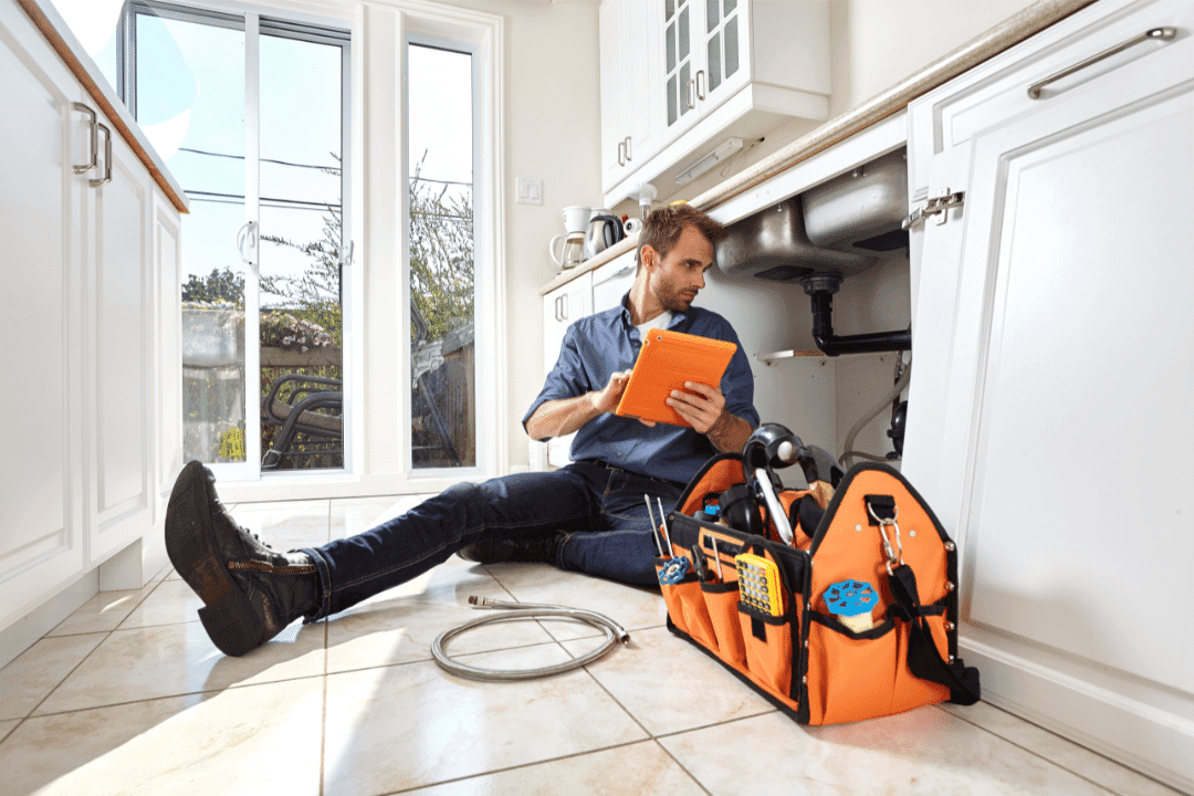 plumber repair man orange bag and clipboard sitting on kitchen tile floor white cabinets sink tools shoes