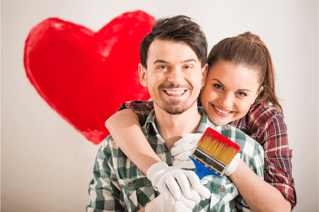 young couple in love red heart relationship painting home improvement plaid shirt smiling hugging