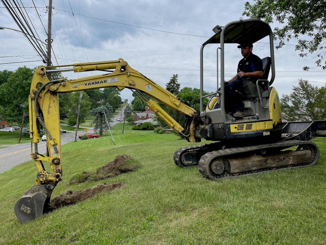 backhoe digging up front yard by