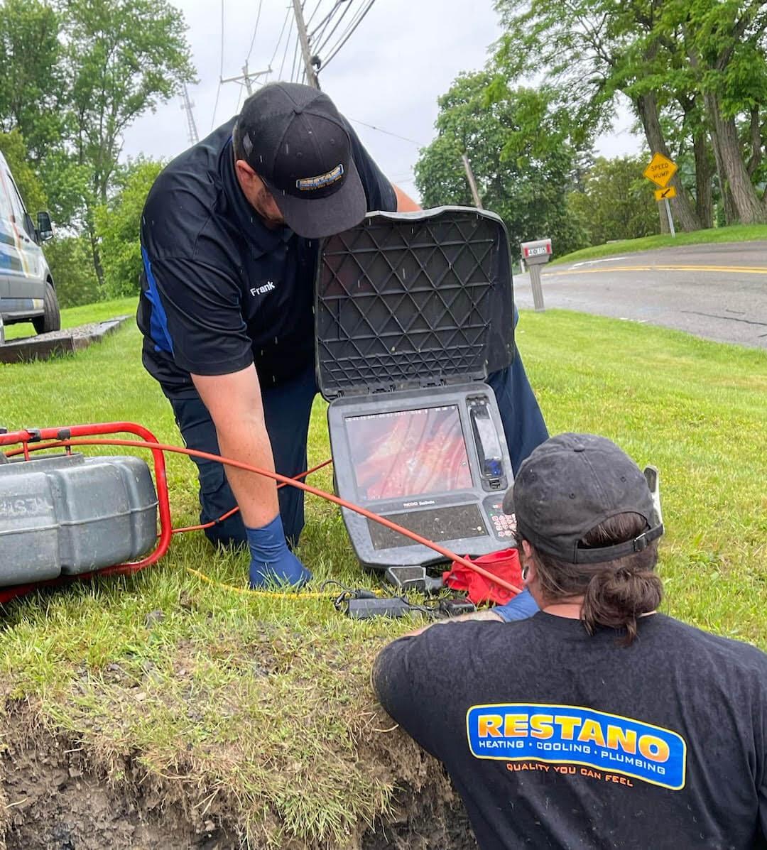 plumbers using computer in yard underground trenchless sewer repair