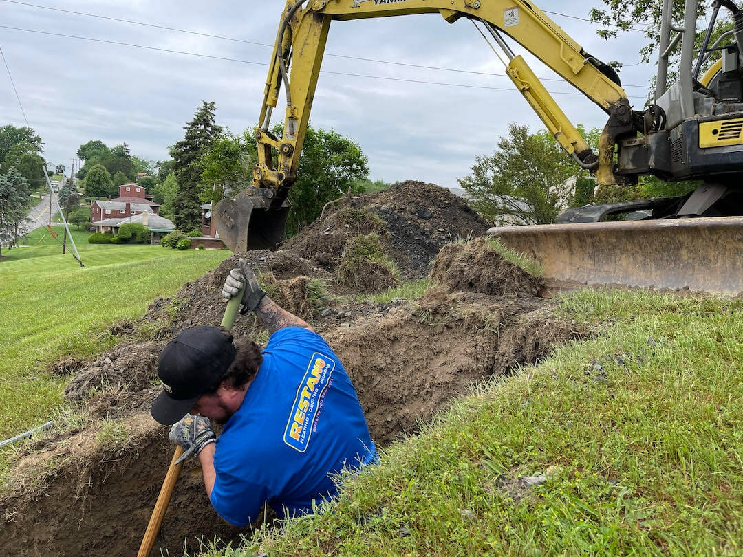 man digging hole with shovel in yard backhoe in the background