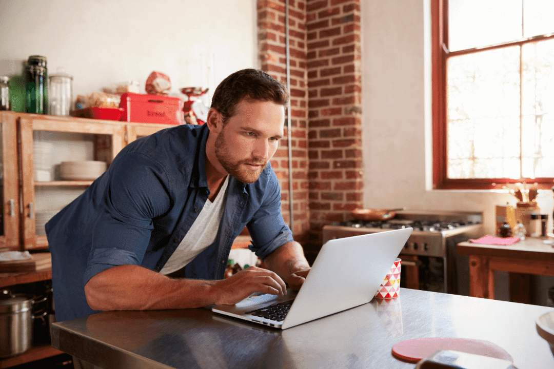 man looking at laptop leaning over doing research in brick apartment