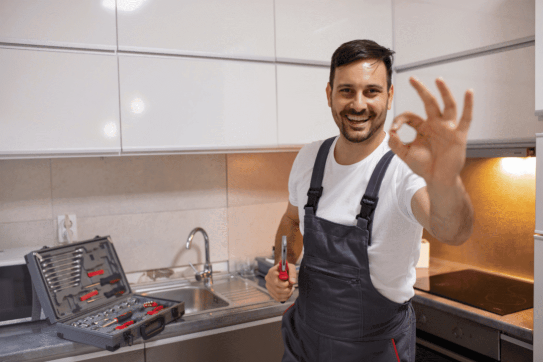 plumber giving ok sign in kitchen working on sink
