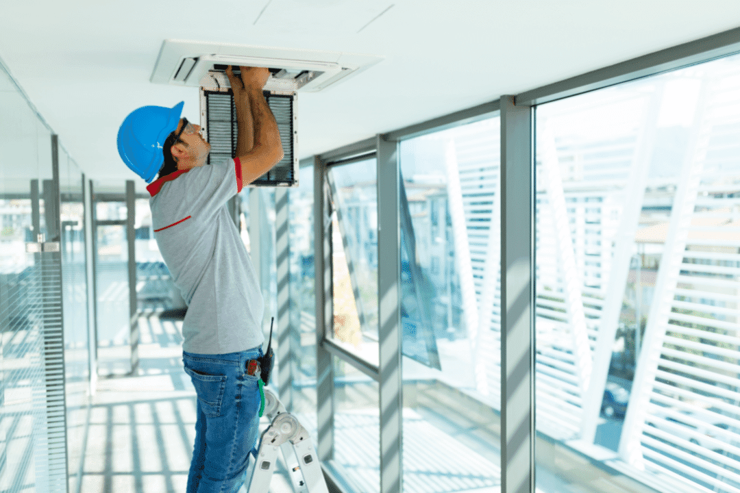 hvac repairman fixing a vent it a bright building