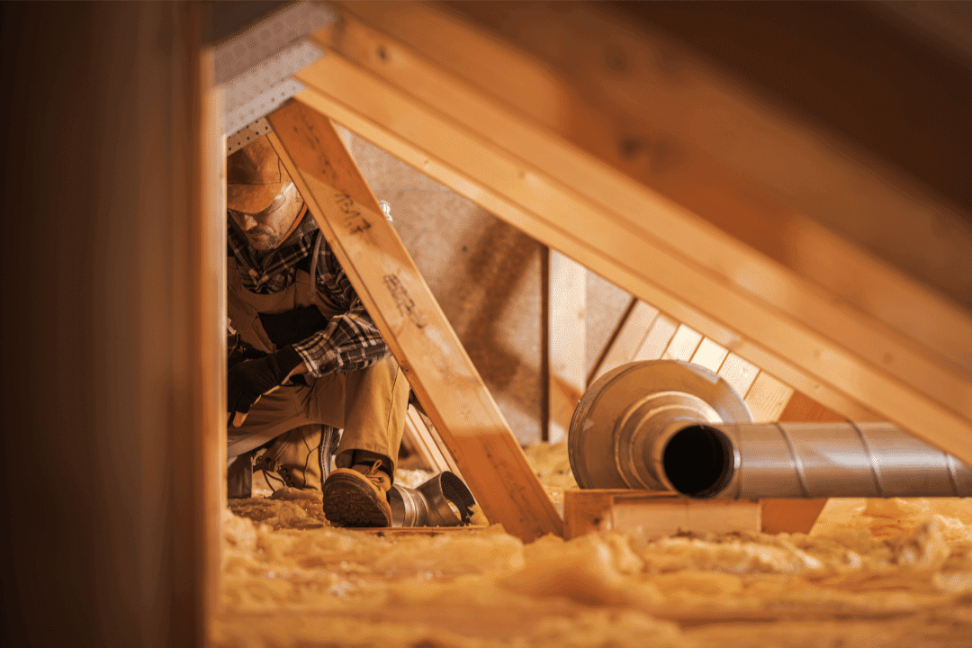 construction worker installing ducts in attic wooden beams