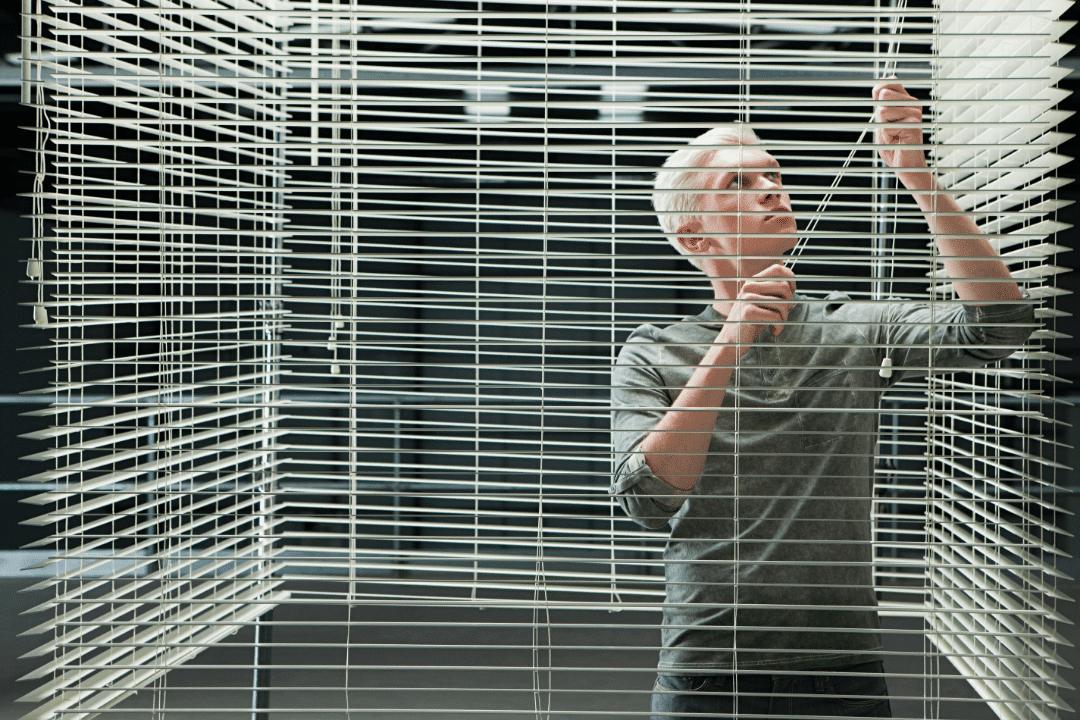 young man closing venetian blinds