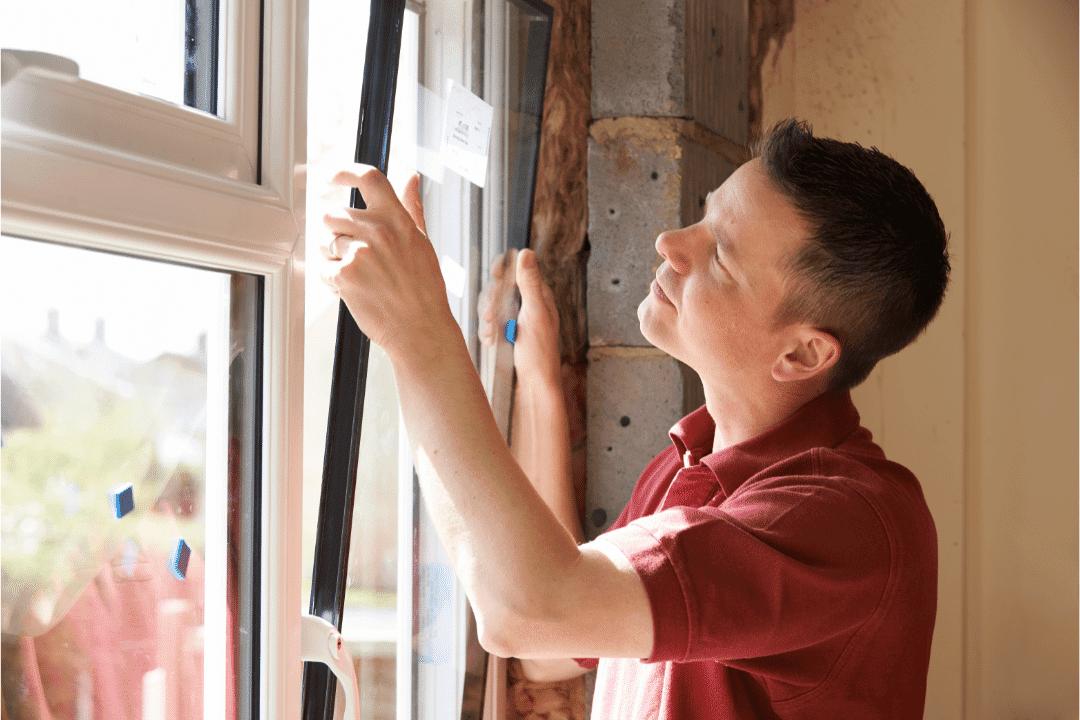 repairman installing window on sunny day