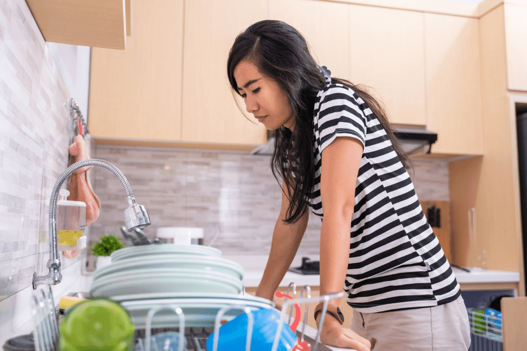 woman looking at sink intently dishes