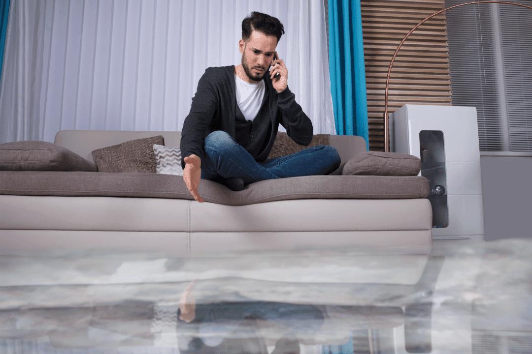 man calling plumber home flooding into living room