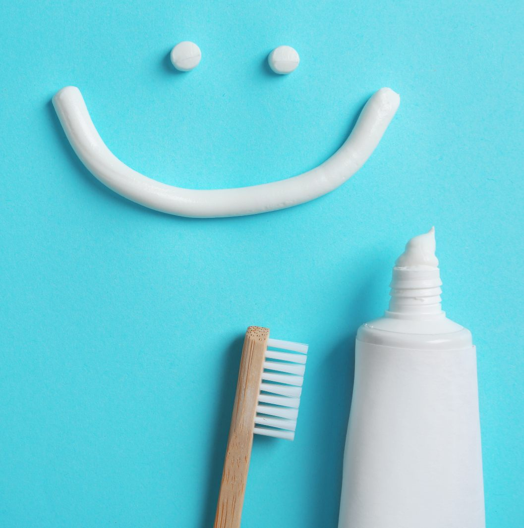 A smiley face with a tooth brush and tooth paste
