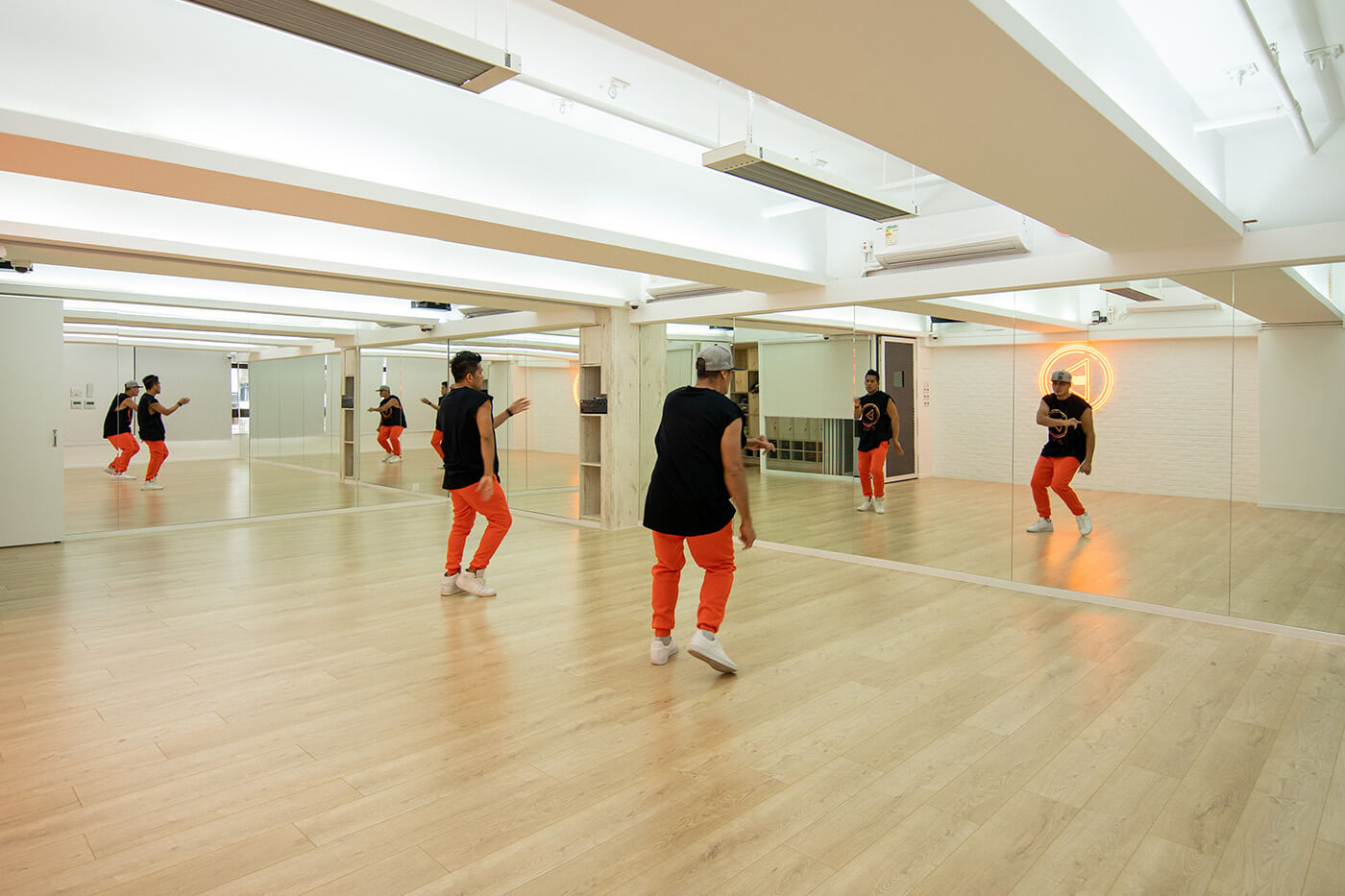 Two bfit dance teachers are practicing at a big dance room with mirrors on two sides.
