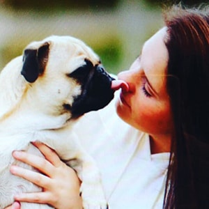 Image of a dog's tongue licking a woman's face to illustrate the need to brush the tongue
