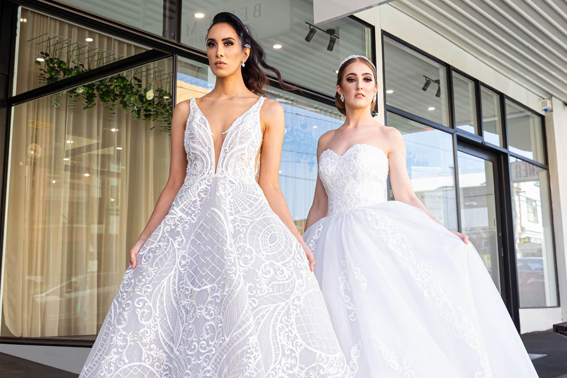 2 models in wedding dresses standing outside of Belle Mariee Bridal