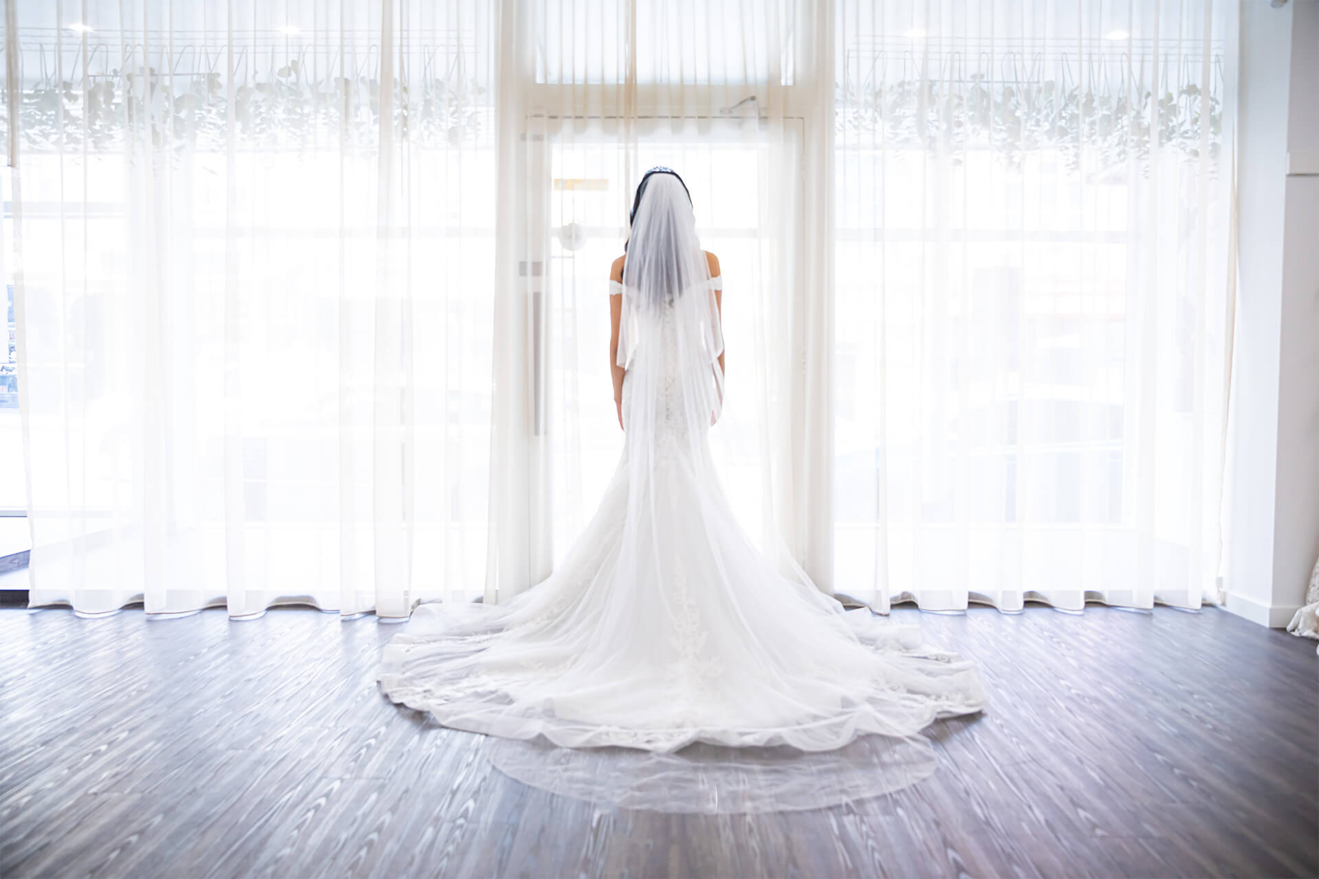 Model in a wedding dress looking out the window with her back turned