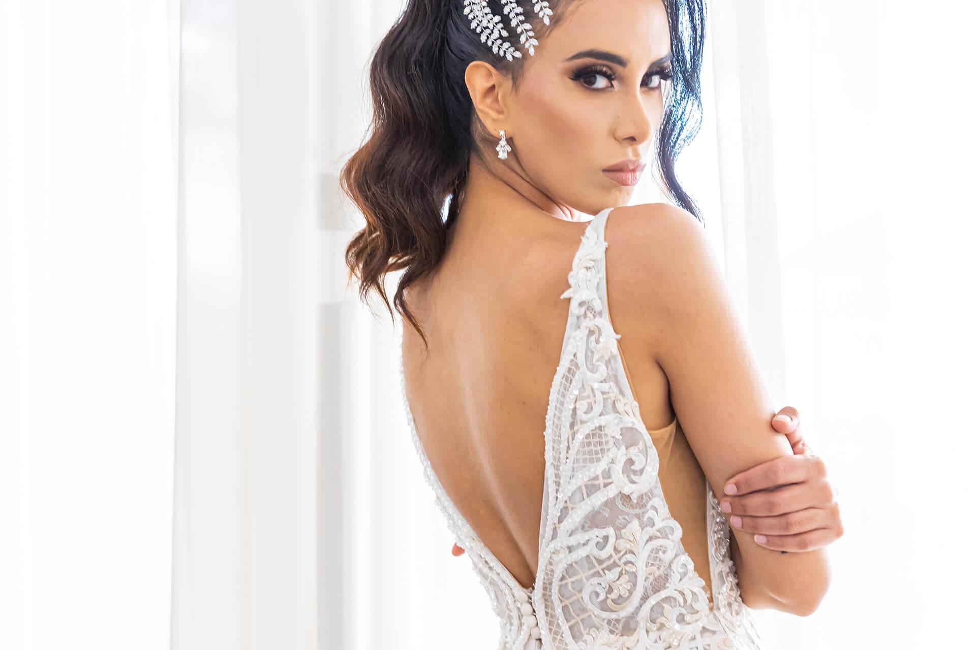 Model in a wedding dress looking over her shoulder