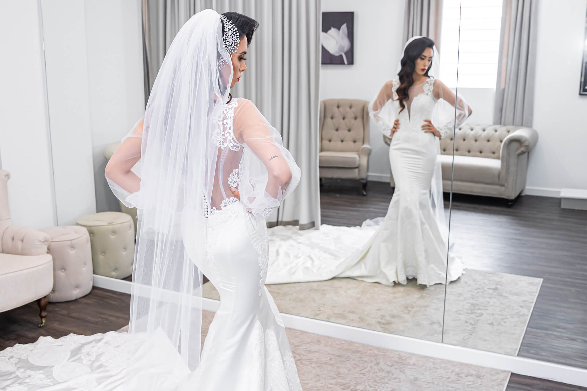 Model in a wedding dress looking at herself in the mirror