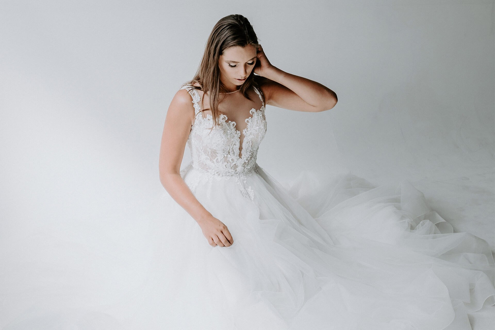 Model in a wedding dress looking down at her dress