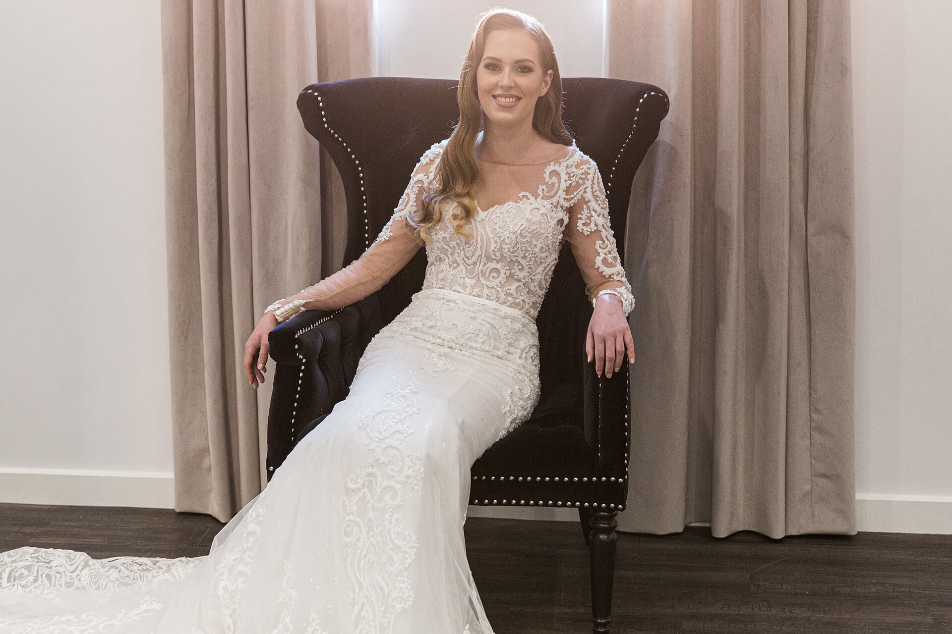 A smiling woman sitting down in a wedding dress