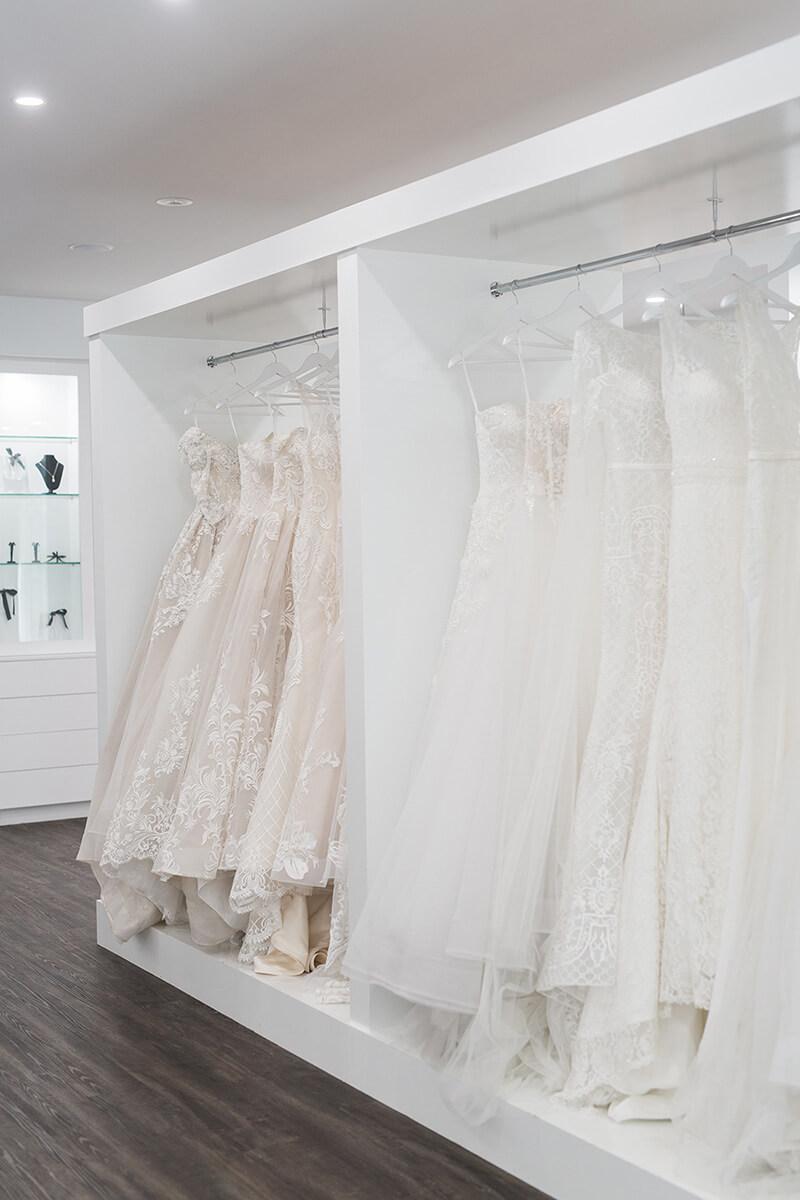 A row of wedding dresses on a rack