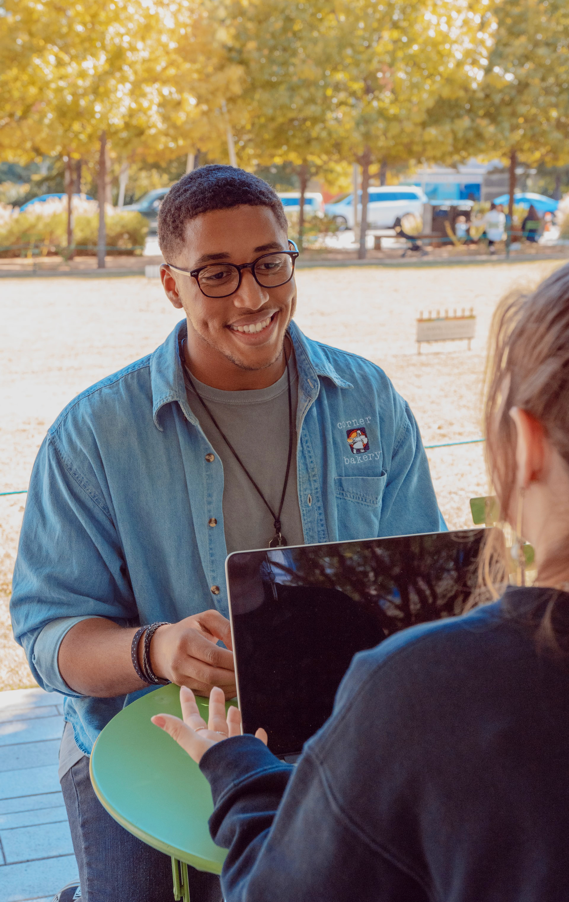 A man smiling while sitting at a table  in a park. He is interacting with a woman with a laptop in front of her.