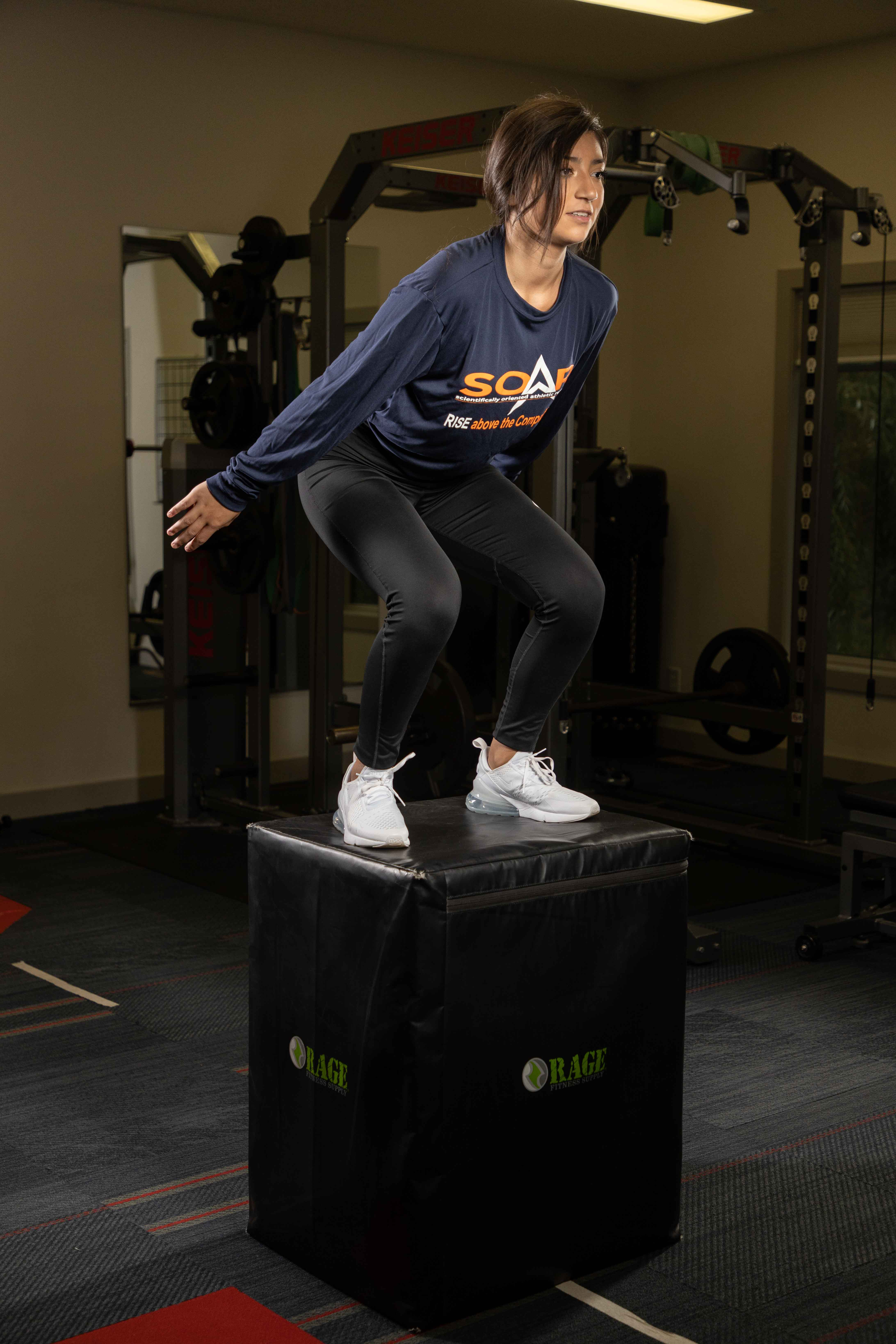 Girl on top of a box after doing a box jump