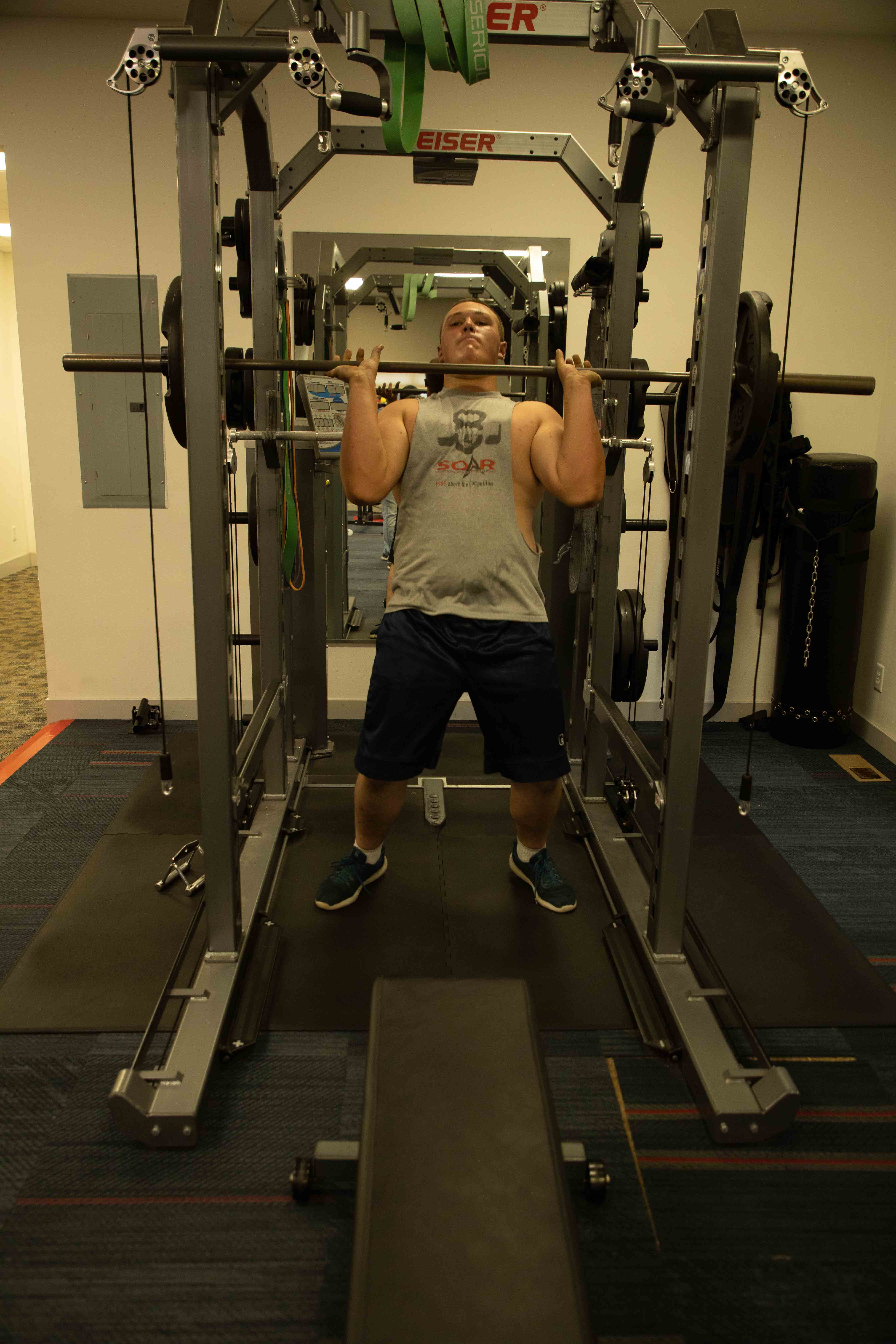 Strong boy doing heavy shoulder presses with a barbell