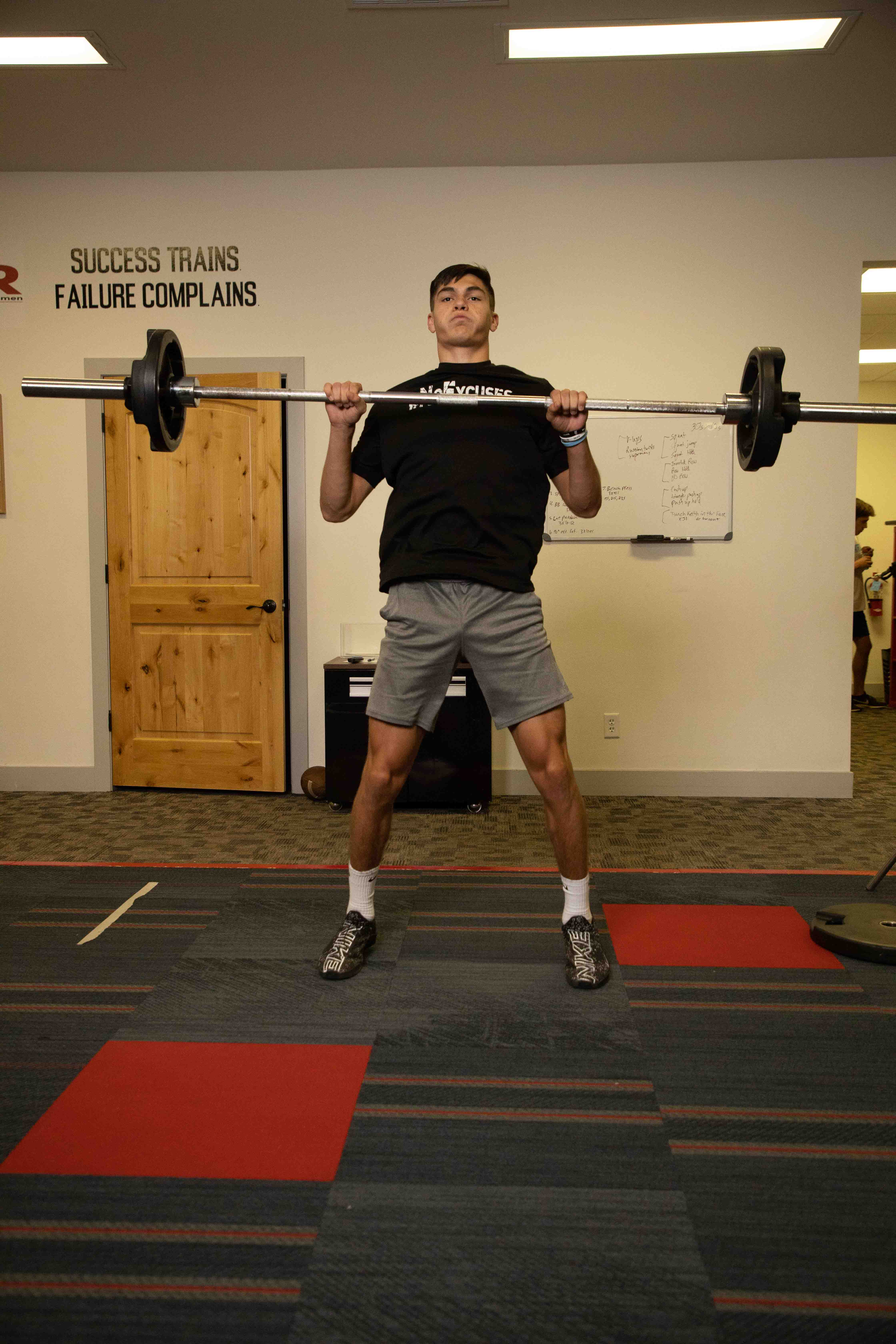 Tall boy mid-exercise with a barbell at chest height