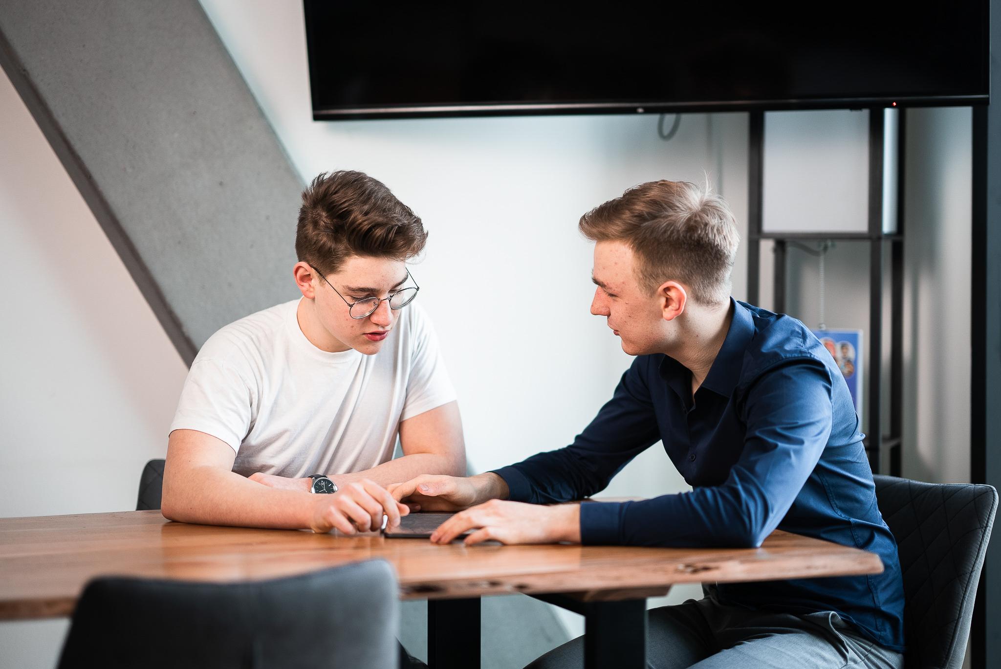 Zwei Junge Männer besprechen etwas mit den Händen auf einem Holztisch