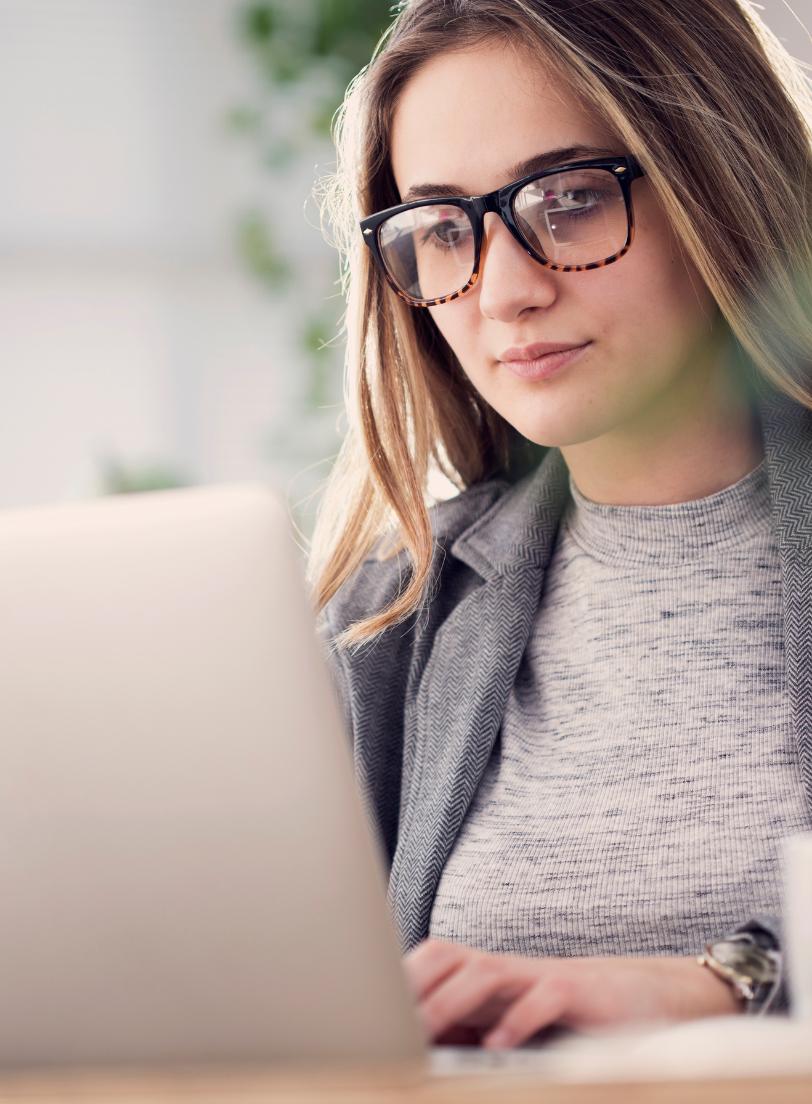 Junge Frau mit Brille liest von Bildschirm