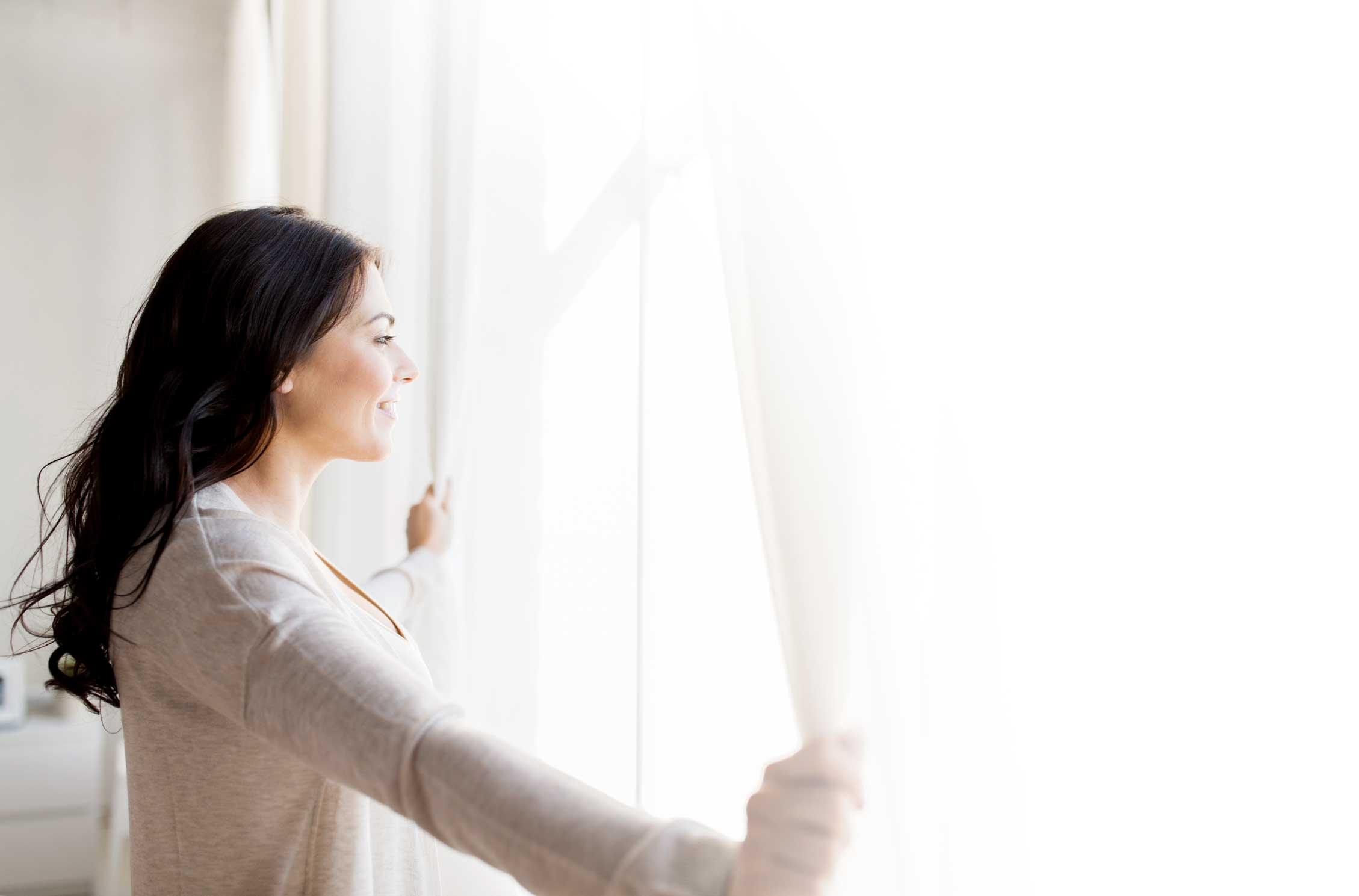Woman smiling looking outside window