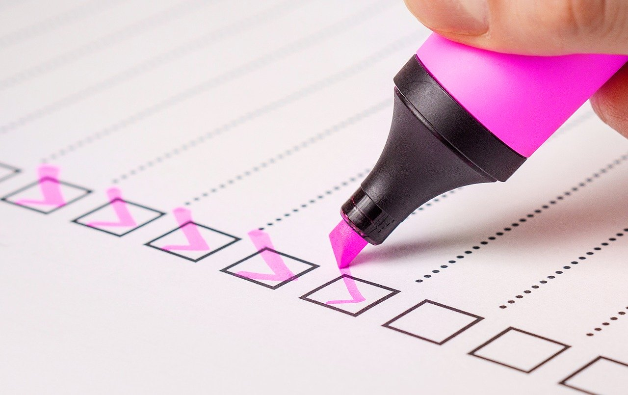 Person using a highlighter to fill out a checklist