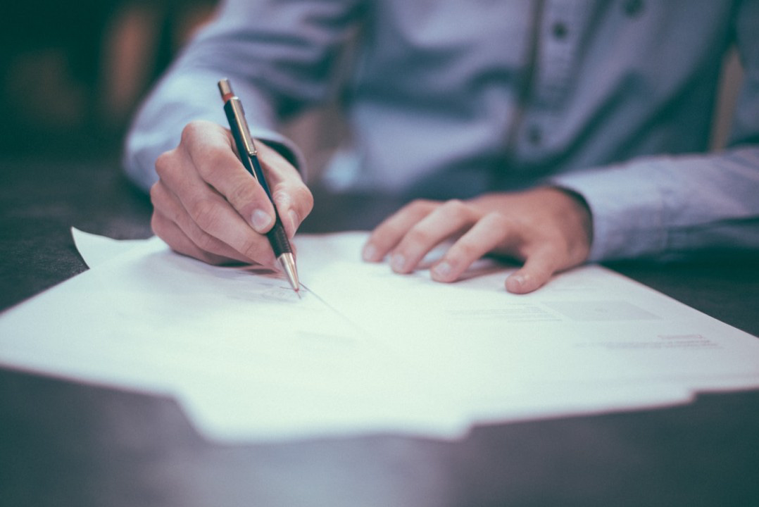 Man using a pen to write on a piece of paper