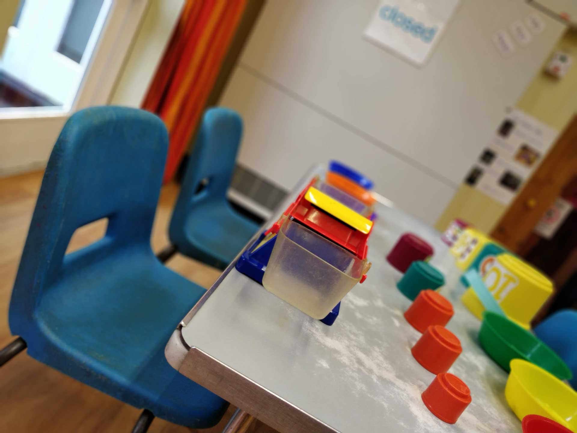 Table and chairs laid out with painting pots and paints at Rottingdean Whiteway Pre-School