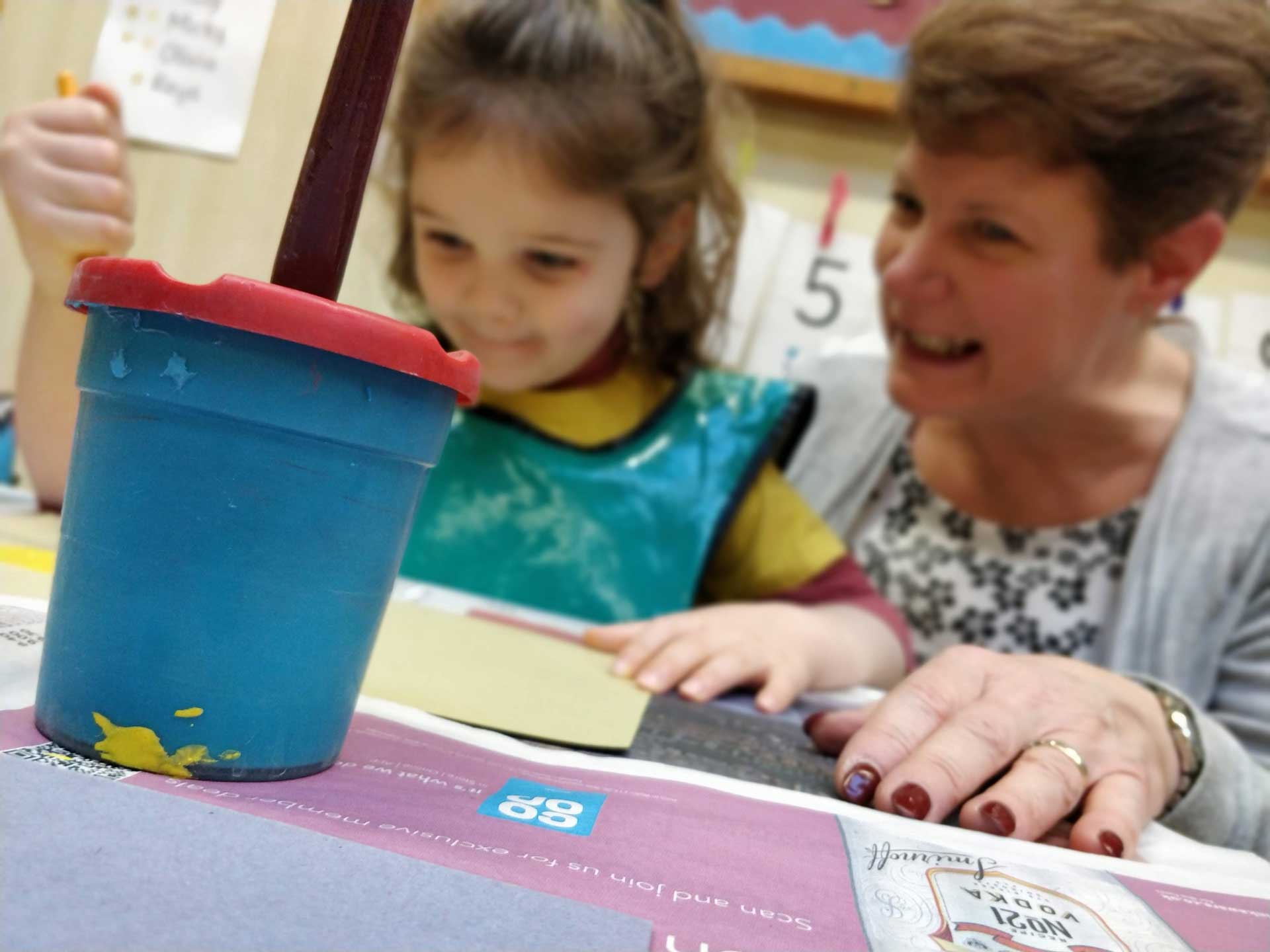A young girl painting with a teacher at Rottingdean Whiteway Pre-School